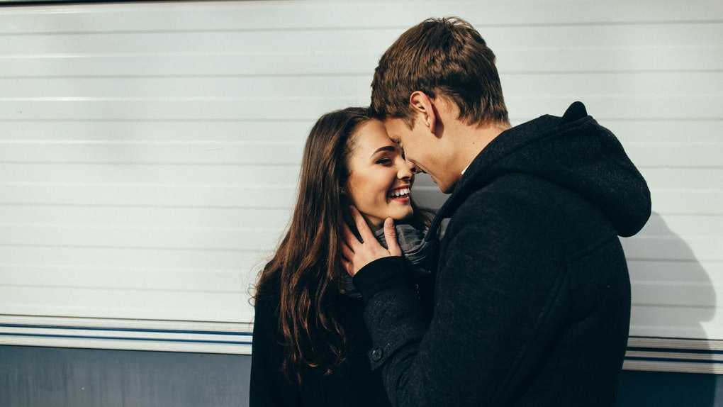 A couple wearing black jackets embraces and smiles outside on a sunny winter day.