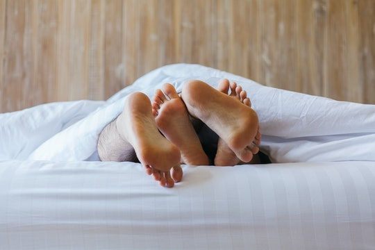 Close up of male and female feet on a white bed. The concept of loving couple having sex under white...