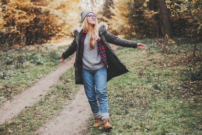 Hiking and travel along in the forest. Concept of trekking, adventure and seasonal vacation. Young woman walking in woods.