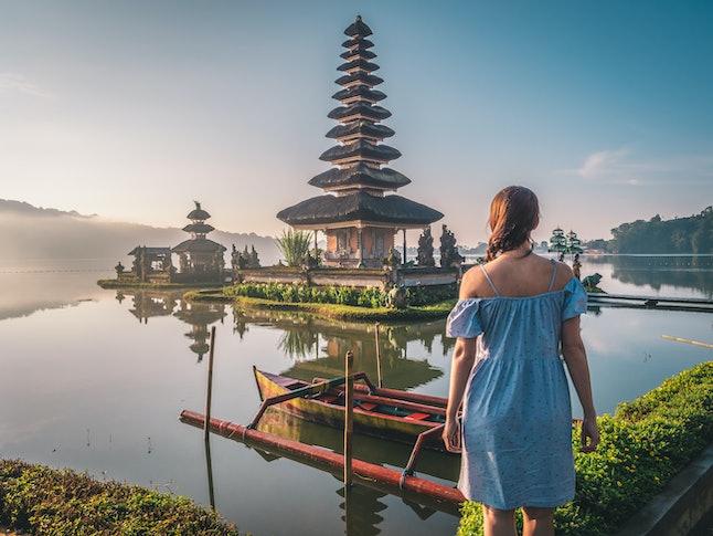 Young woman near Pura Ulun Danu Bratan temple near Beratan lake in Bali island, Indonesia at sunrise. Iconic image of Bali and southeast asia. Travel and adventure background image.