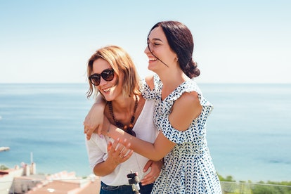 Two happy women hugging, standing on blue sky and sea background, stylish woman, bracelets, necklace, natural make up, beauty face, girl resting, attractive, skin care, good emotions, positive, happy