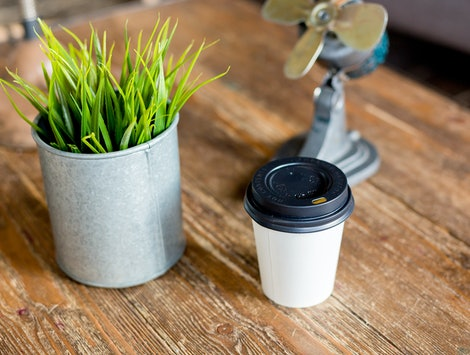 paper Cup of coffee on a wooden table next to a pot of green grass and light grey background on the sofa