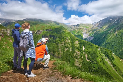 Group of travellers enjoying view mountains during summer vacation in Georgia (country).Beautiful inspirational landscape, travel and activity.