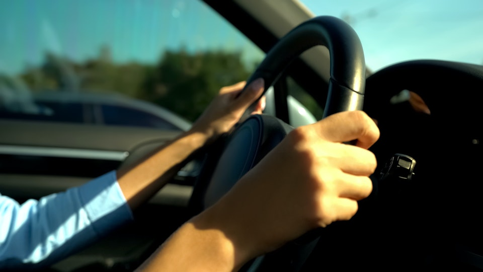 Female hands holding steering wheel, woman passing driving exams at school