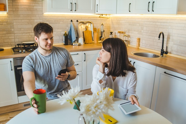 couple talking at the kitchen in the morning drinking tea. domestic life concept