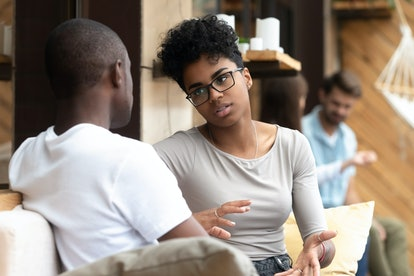 Focused African American woman talking with man in cafe, girlfriend discussing relationships with bo...