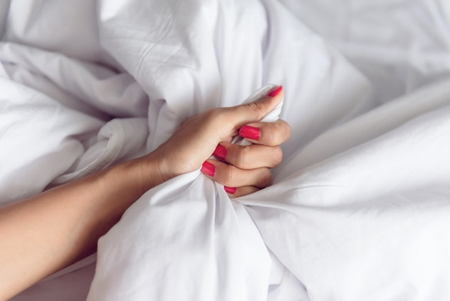 Hand sign orgasm of woman on white bed , Hand of female pulling white sheets in ecstasy , feeling and emotion concept