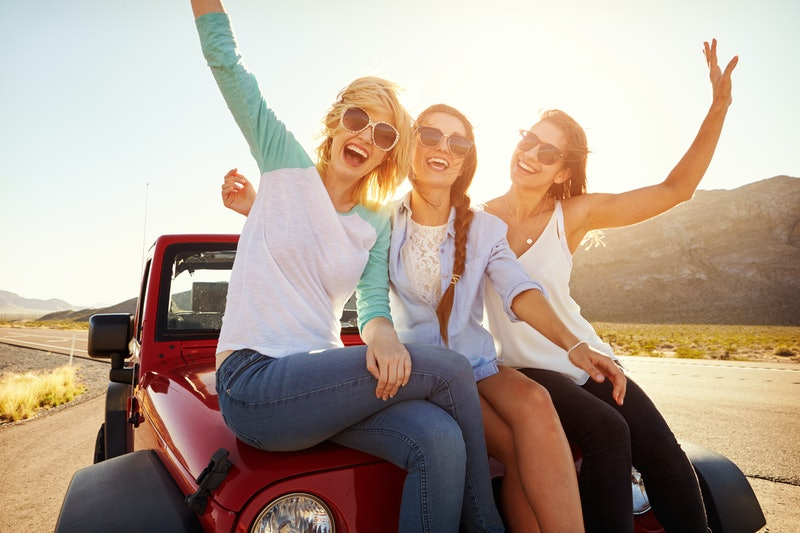 Three Female Friends On Road Trip Sit On Car Hood