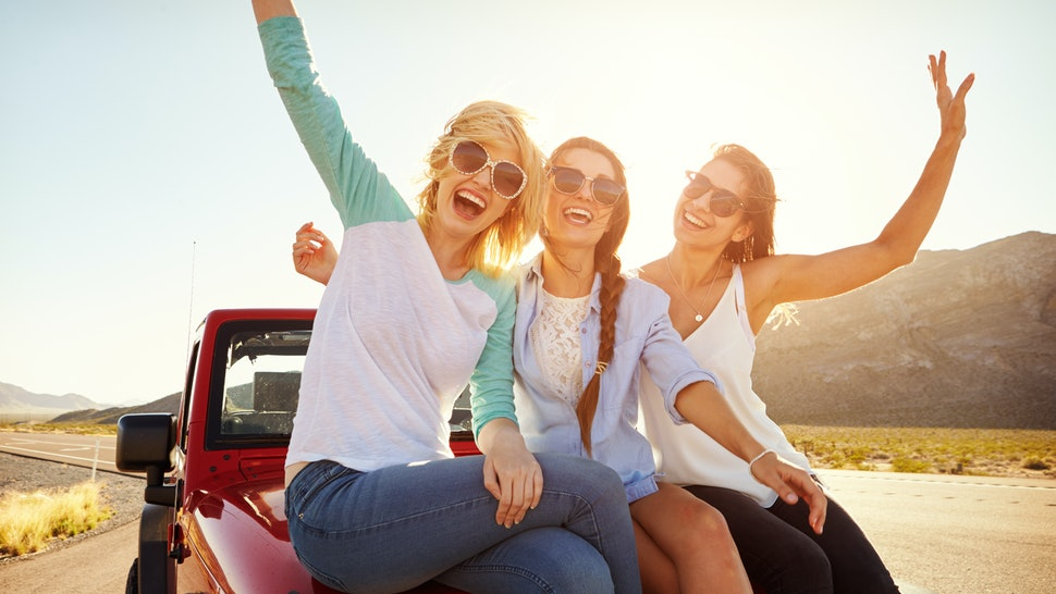Three Female Friends On Road Trip Sit On Car Hood