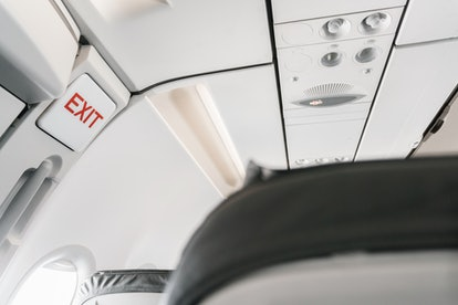emergency exit sign on airplane. Empty airplane seats in the cabin. Modern Transportation concept. Aircraft long-distance international flight