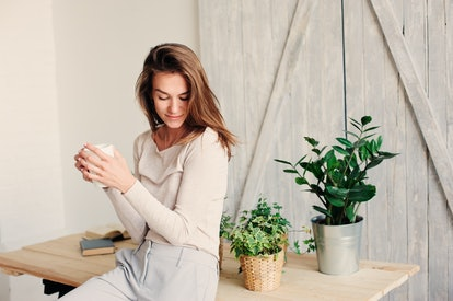 beautiful young feminine woman relaxing at home in lazy weekend morning with cup of coffee, wearing casual fashion clothes