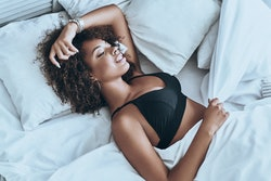 Lost in her dreams. Top view of attractive young African woman in black lingerie keeping eyes closed...