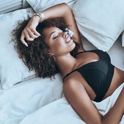 Lost in her dreams. Top view of attractive young African woman in black lingerie keeping eyes closed and smiling while lying in the bed at home