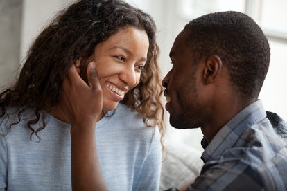 Happy African American couple having date at home, sitting together on couch, loving man touching a...