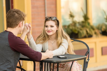 Young couple sitting at an outside table engaged in conversation.