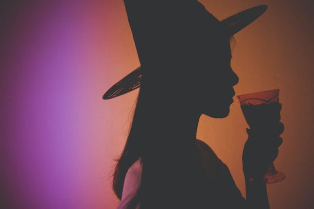 Shadow image of a woman wearing a witch's hat and holding a glass of drink with orange and purple light in the background. Halloween.