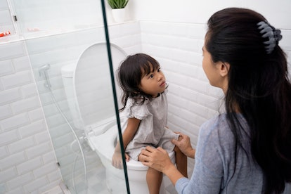 mother help her kid to use toilet. toilet training for toddler with mom