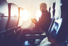 Man entrepreneur is watching video on mobile phone, while is sitting in plane near window with sun r...