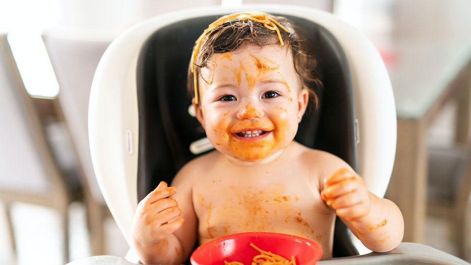 child girl, eating spaghetti for lunch and making a mess at home in kitchen