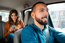 Smiling driver talking with female passenger. Woman using mobile phone in the background.