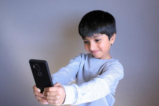 Kid looking at smartphone taking selfie. Indian Boy smiling taking photo of self. Kid taking selfie....
