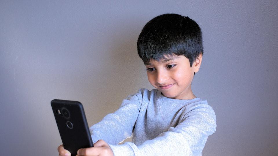 Kid looking at smartphone taking selfie. Indian Boy smiling taking photo of self. Kid taking selfie.shot in natural light, selective focus. Indian kid taking selfie.
