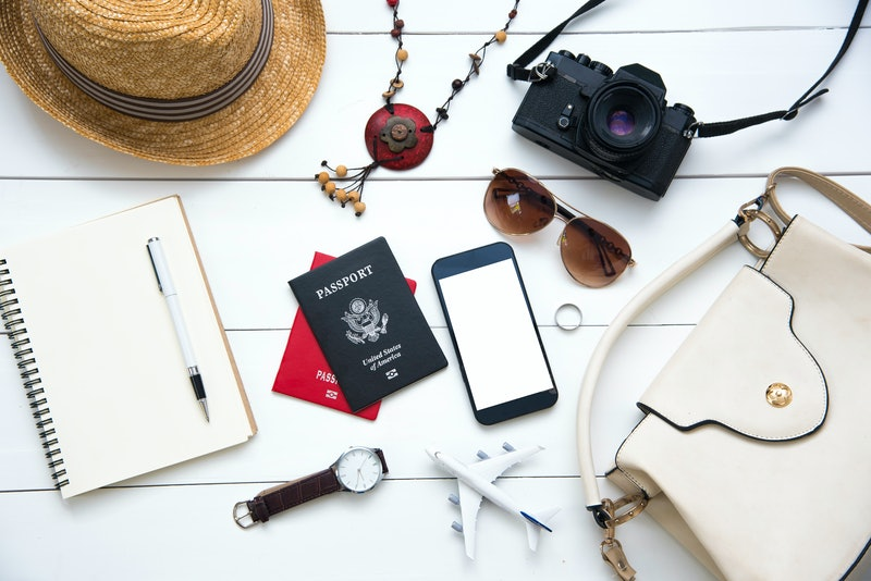 Travel accessories costumes for women. Passports, The cost of travel maps prepared for the trip on white wood floor