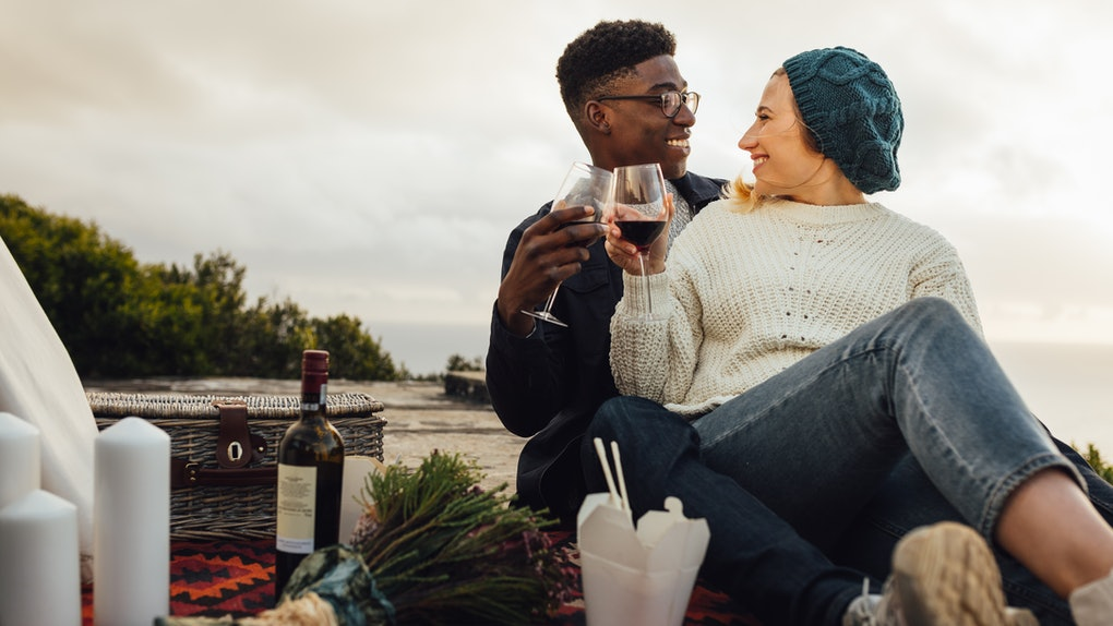 Man and woman toasting wine glasses at the picnic. Couple having wine on a romantic date outdoors.