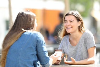 Two happy women talking sitting in a park a sunny day