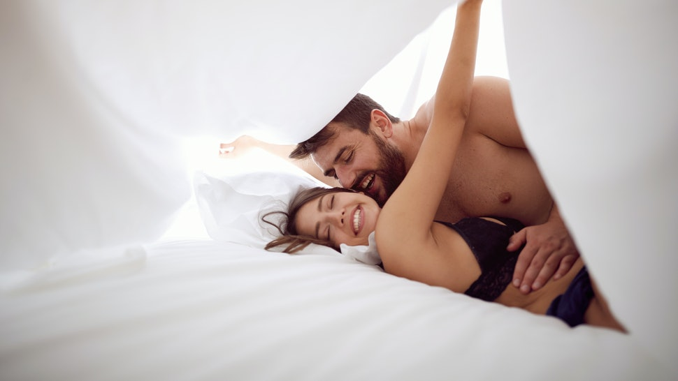 happy man and woman is lying in bed together. Enjoying the company of each other.