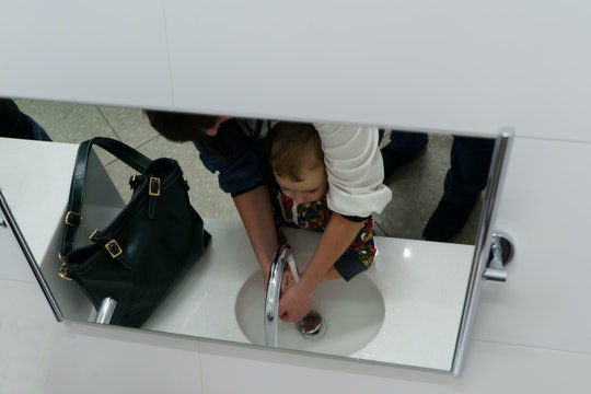 Mom wash hands son in the public restroom