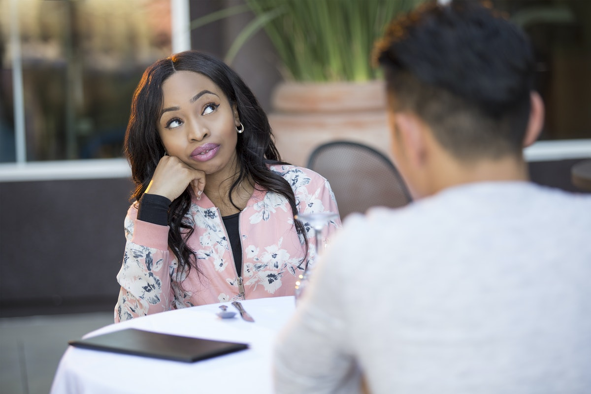 Black female disinterested with a blind date at an outdoor restaurant.  They are sitting and chattin...