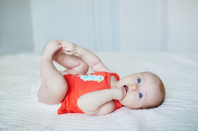 Cute baby girl lying on her back and touching her feet. Happy healthy kid at home in nursery