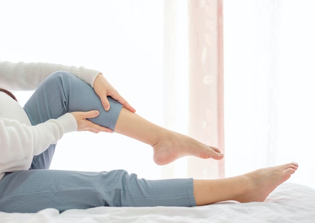 Pregnant women with cramp in leg. Copy space.