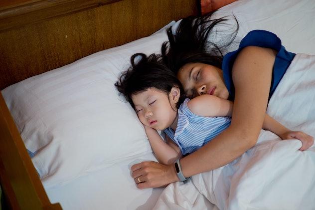 asian girl sleep on bed with mom, kid sick, child sleep