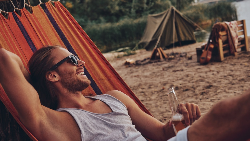 Real relaxation. Handsome young man keeping hand behind head and smiling while lying in hammock