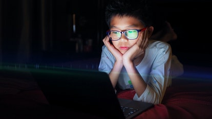 Asian boy lying in bed and watching laptop at night.