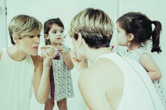 Beautiful mom showing how to use lipstick. Adorable girl looking at herself in mirror and imitating mothers action. They getting dressed for walk together. Mother and daughter concept