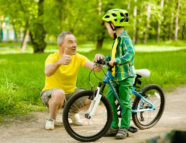 Grandfather talking with his grandson riding a bicycle