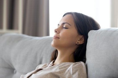 Serene calm woman relaxing leaning on comfortable couch having nap breathing fresh air dreaming, lazy relaxed girl lounging with eyes closed on sofa enjoy stress free peaceful day wellbeing at home