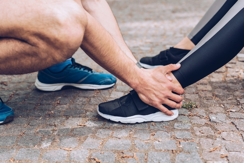 cropped shot of sportsman touching injured leg of sportswoman in sneakers