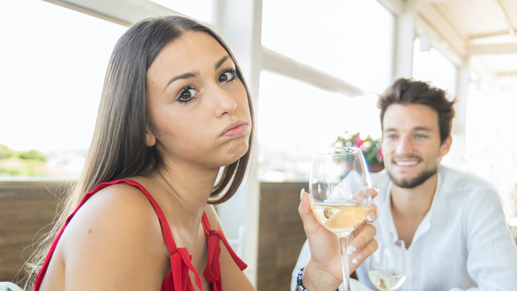 Young woman making an exasperated expression gesture on a bad date at the restaurant