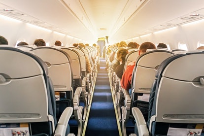 Commercial aircraft cabin with rows of seats down the aisle. morning light in the salon of the airli...