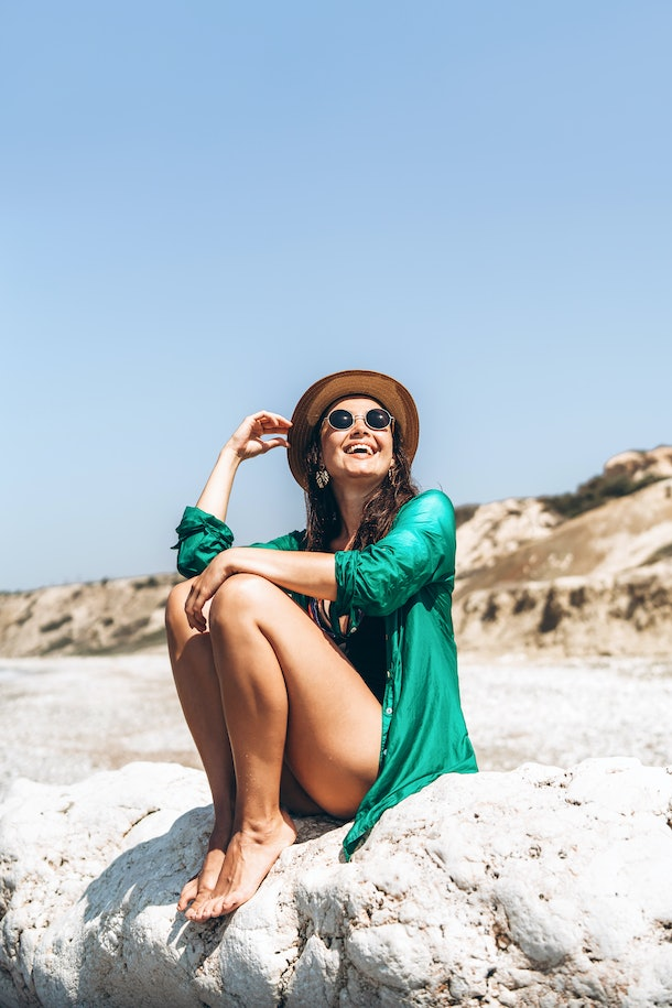 Pretty pan asian travel girl relaxing on the beach at the sea in green pareo