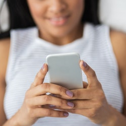 A woman reads from her phone in bed.