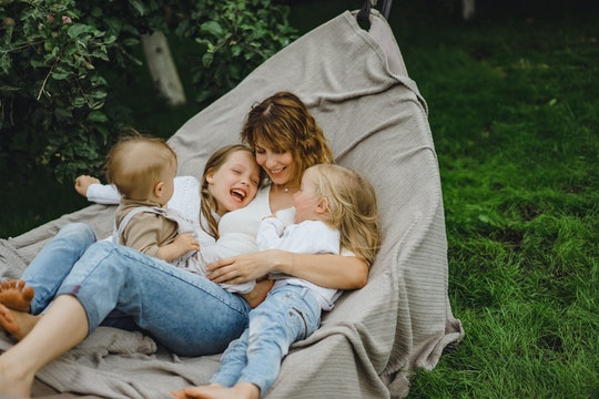 mother with children having fun in a hammock. Mom and kids in a hammock. The family spends time with...