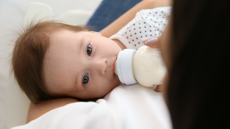 Woman feeding her baby from bottle at home, closeup