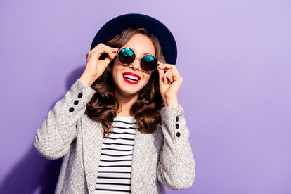 Portrait of funny carefree girl holding eyelets of glasses with two hands having rest relax isolated on violet background, wearing striped street outfit style