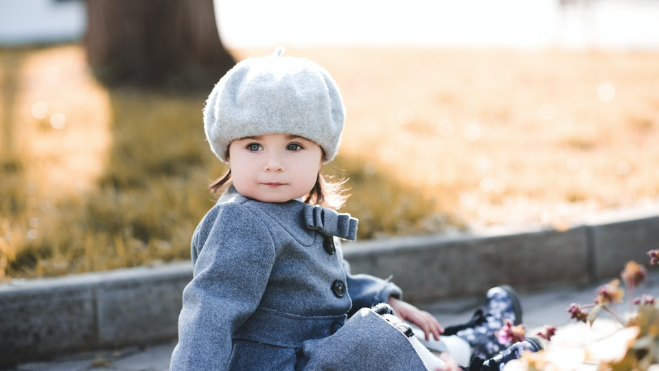 Funny baby girl wearing stylish winter jacket and beret outdoors in park. Autumn season. CHildhood.