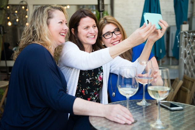 Women friends enjoying white wine and taking selfies while smiling and laughing at wine bar